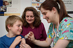 A boy recieves a shot from a health professional.